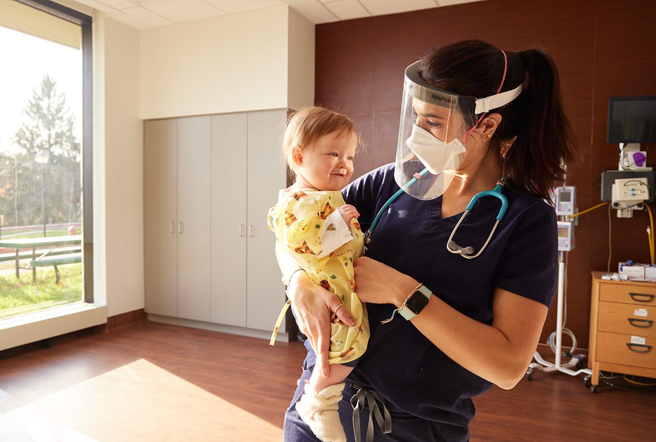 A nurse holding an infant